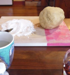 Marzipan ball on a board with icing sugar, ready to be divided up and rolled into logs